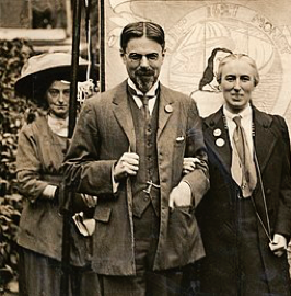 Laurence and Clemence Housman wearing Suffrage Badges and standing in front of a Suffrage Banner, circa 1911. LSE Library. Wikimedia Commons.