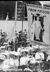 "Newspaper photo showing ""From Prison to Citizenship"" banner in Coronation Procession"