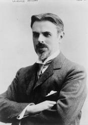 Photographed half portrait of Laurence Housman turned slightly to his left with crossed arms, wearing a suit, tie, and pocket square