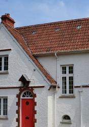 Close-up photo of white 1920s house with red door and steep red tiled roof