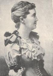 L.T. Meade, the first editor of Atalanta. In this image, she is portrayed in half-body portrait, from head to waist, in a Victorian dress. She is facing almost 90 degrees to the left. Her hair is neatly brushed with small bun. An earring is shown on her right ear.