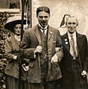 Photograph, printed, paper, monochrome, Laurence and Clemence Housman wearing suffrage badges and standing in front of a suffrage banner. LSE LIbrary. Wikimedia Commons